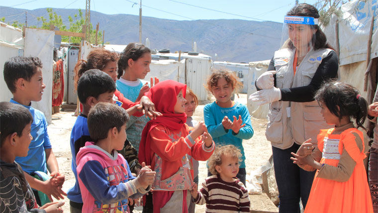 World Vision staff show children in a refugee camp how to stay safe from COVID-19