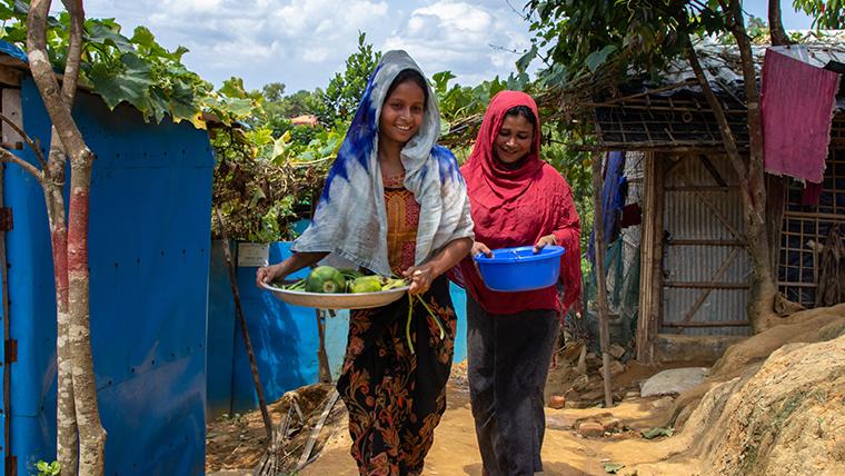 Rohingya women walk together through the refugee camp