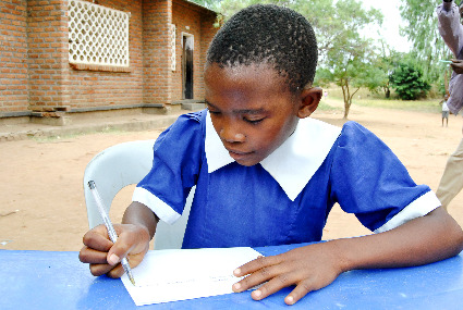 Maria, a World Vision sponsored child from Malawi, writing a letter.