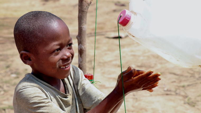 A young boy uses a tippy tap