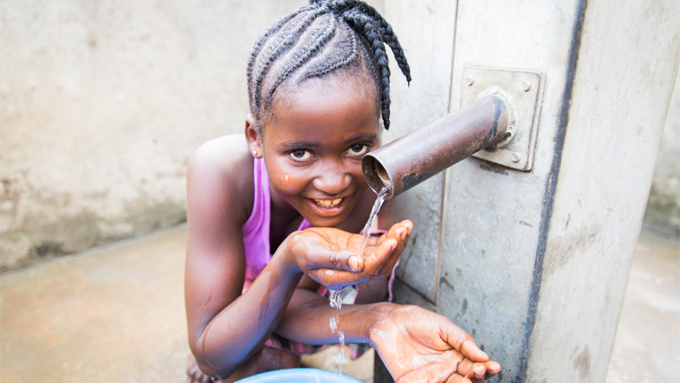 Isata drinks clean water from the fresh source near her home