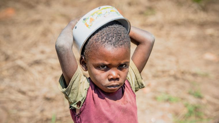 A child waits for food at a Child Friendly Space near Kananga, DRC