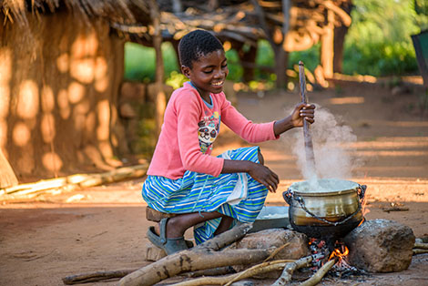 Rosemary helps with the cooking, at home in Zambia