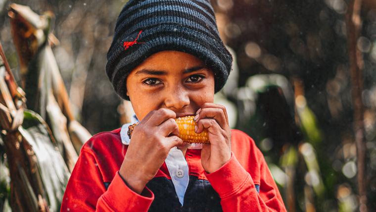 Victor, outside his mountain home, eats corn on the cob
