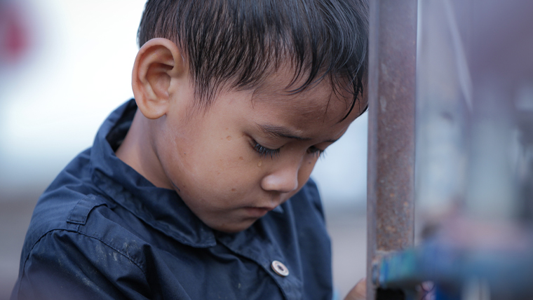 A young boy in Cambodia lowers his head sadly