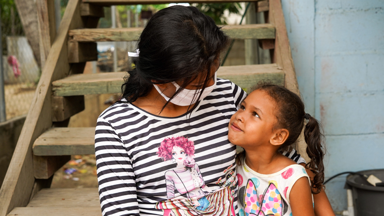 Ana (wearing a face mask), hugs her 5-year-old daughter, Briana, on the steps outside the home in Honduras