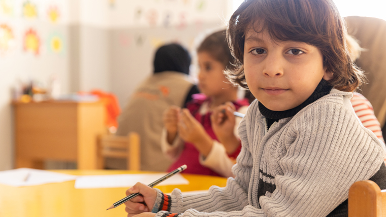 In Lebanon, five-year-old Mouataz enjoys being creative at the Child Friendly Space centre with other child refugees from Syria.