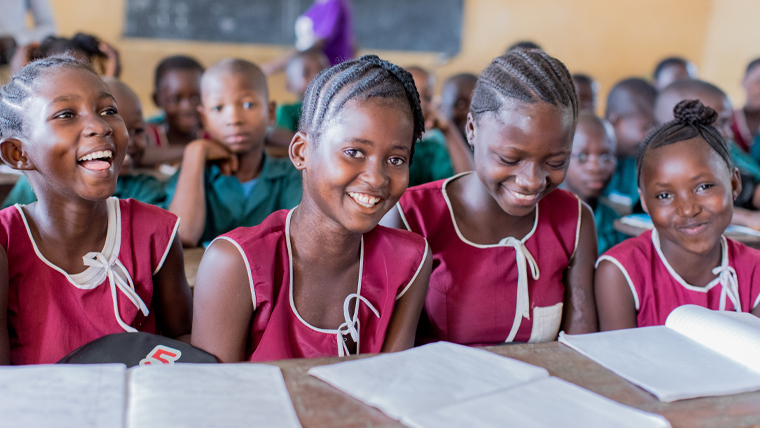Isata sits with her friends in the classroom