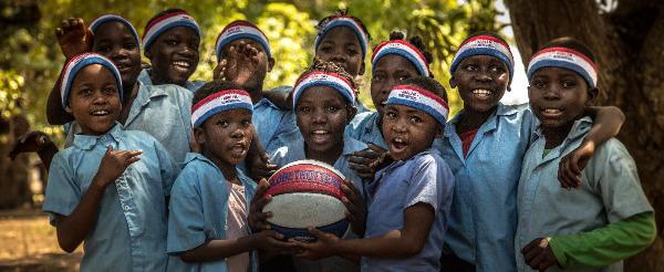 Children wearing Harlem Globetrotter headbands, holding a basketball.