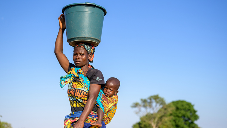 A mother in rural Malawi carries a large bucket of water on her head, while her young baby is swaddled on her back.