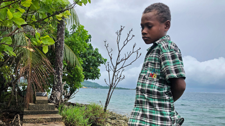 Timothy, 13, visiting his family's old home in the Solomon Islands
