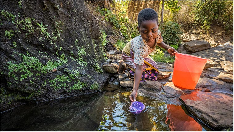 Ireen at the water hole, scooping water into her bucket