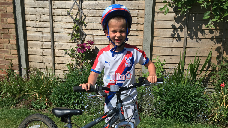 Joel, 6, on his bike after completing his fundraising laps in the garden