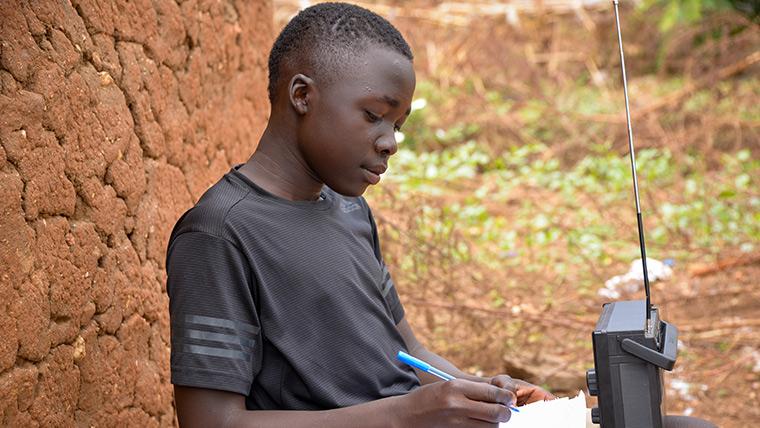 15-year-old Simon uses a radio to keep studying in Bidibidi refugee settlement in Uganda during coronavirus.
