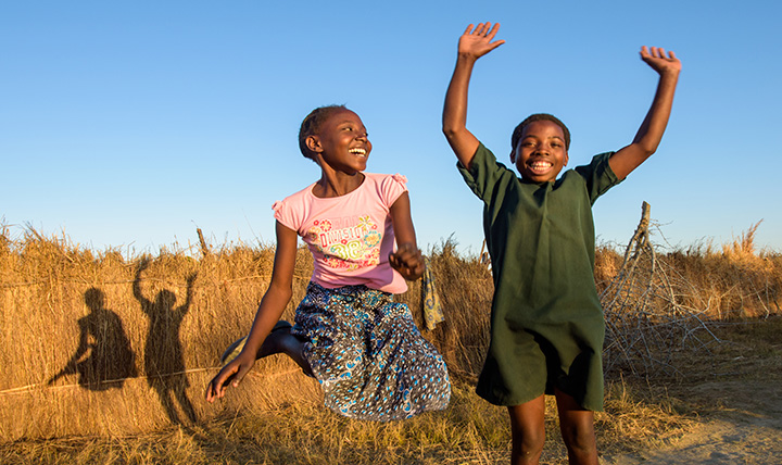 Everlyn, 13 and Clara, 12 jump for joy in front of World Vision borehole in Zambia
