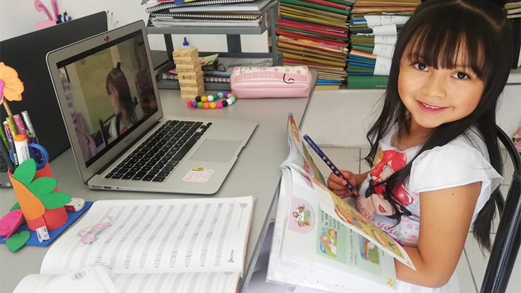A young girl sits at a table with laptop and books in front of her.