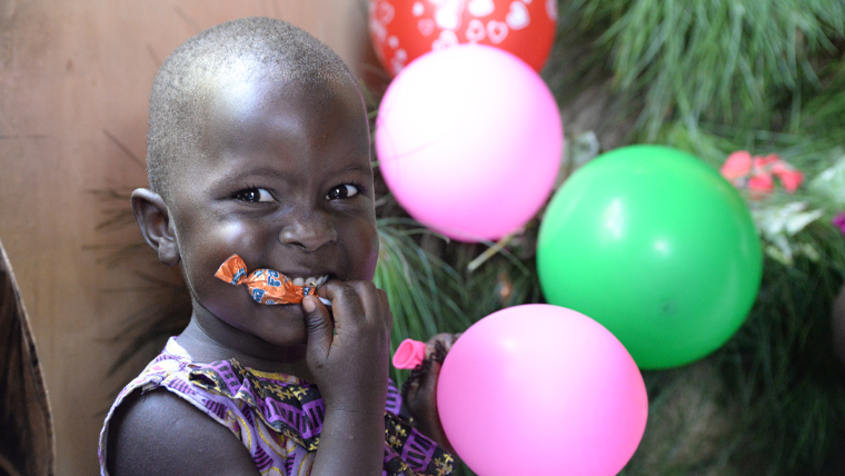 A little girl in Uganda enjoys a sweet at a community Christmas celebration