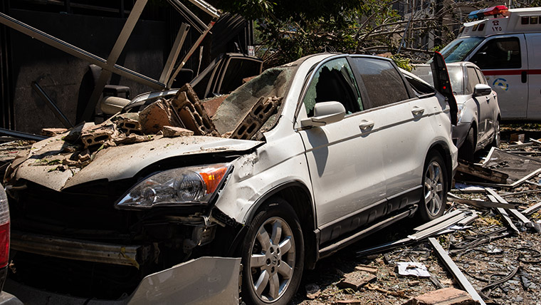 A car crushed by falling debris, following the enormous explosion at Beirut's port
