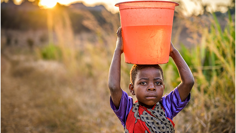 Ireen, 8, carries the precious water home