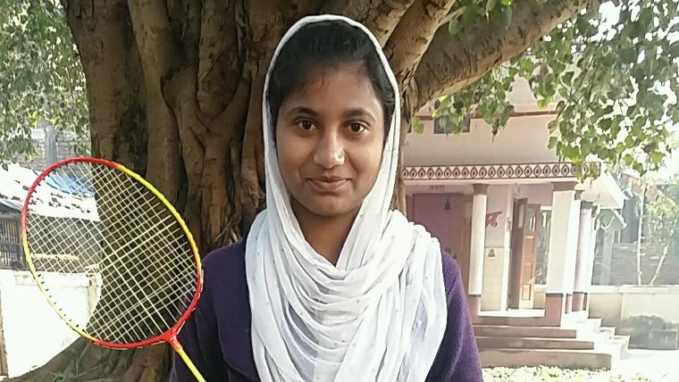 Sponsored child, Sama, holds her badminton racket