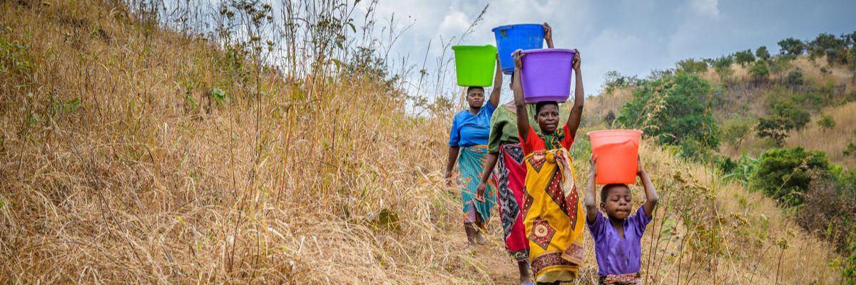 Children walking with buckets
