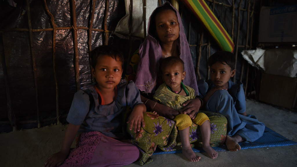 A mother and her children sit after fleeing violence