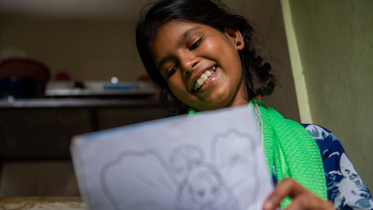 In India, 11-year-old Archana colours a picture using gifts from her child sponsor. She treasures all of them, especially the crayons, colours and colouring books.