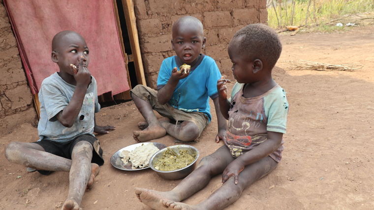 Children in a camp in South Sudan eat cassava leaves with maize flour prepared by their mother, Alawia