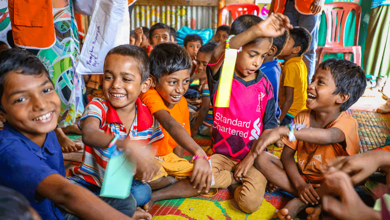 Refugee children in Bangladesh show the buddy bracelets made for them by children in the UK last year