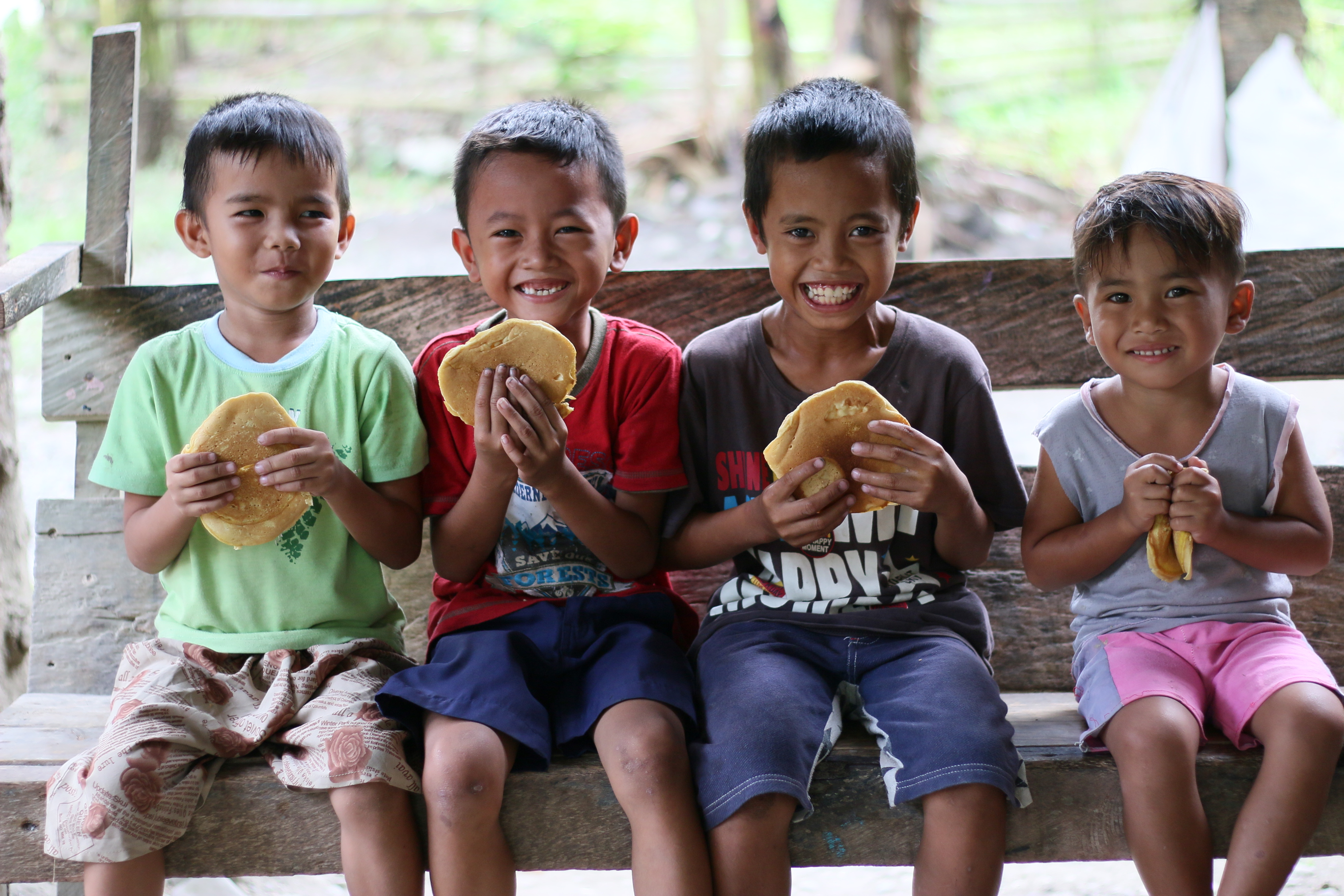 6-year-old Kenneth (red top) and his friends, in the Philippines, enjoy freshly cooked pancakes together